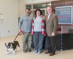 (L to R): Thor, Jeff Claudio's service dog; Jeff Claudio; Leonora Claudio; NWFSC President, Dr. Devin Stephenson.